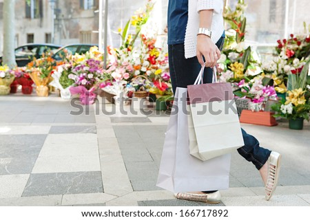 Side view of the lower body section of a young woman walking passed a fresh flowers market stall carrying paper shopping bags during a sunny day outdoors. Faceless figure. - stock photo