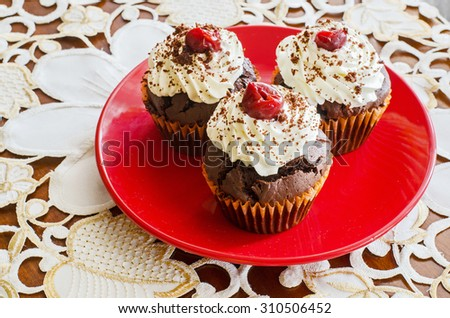 side view of three chocolate muffins with whipped cream and cherry on top on a red plate on a white decorated table cloth  - stock photo