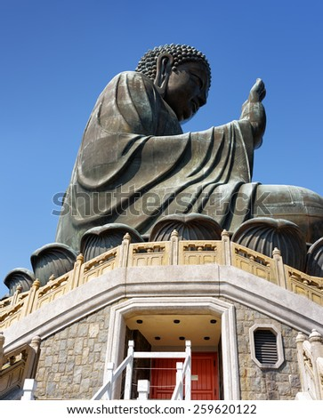 Side view of Tian Tan Buddha (the Big Buddha) on the blue sky background. Red doors leading into a temple under the bronze statue in Hong Kong. Hong Kong is popular tourist destination of Asia. - stock photo