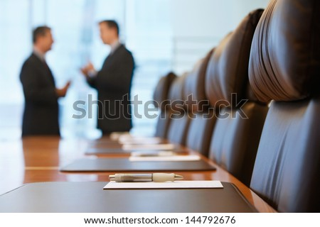 Side view of two blurred businessmen talking in conference room - stock photo