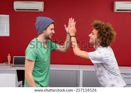Side view of two casual young businessmen high fiving in office - stock photo