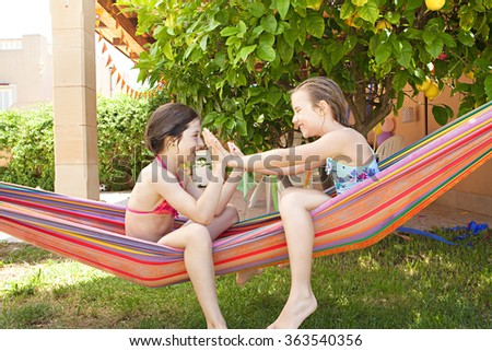 Side view of two children girls friends playing games together in a summer home garden holiday, relaxing sharing a colorful hammock and laughing outdoors. Fun recreational lifestyle, sunny vacation. - stock photo