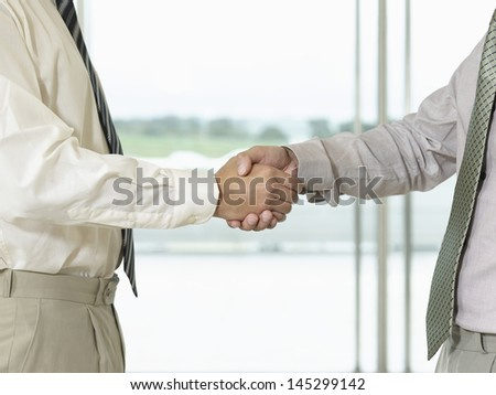 Side view of two cropped businessmen shaking hands - stock photo