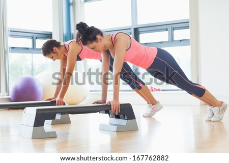 Side view of two fit women performing step aerobics exercise in gym - stock photo
