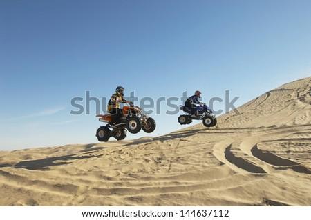 Side view of two men doing wheelies on quad bikes in the desert - stock photo