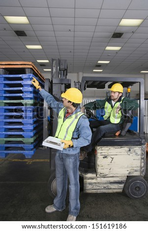 Side view of two multiethnic young men working in factory - stock photo