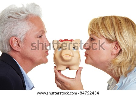 Side view of two senior women kissing a piggy bank - stock photo