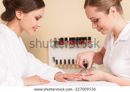 Side view of two woman sitting and smiling at spa salon. Beautician trimming cuticles of female client - stock photo