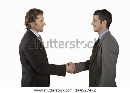 Side view of two young businessmen shaking hands on white background - stock photo
