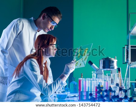 side view of two young caucasian researchers studying a sample in a laboratory - stock photo
