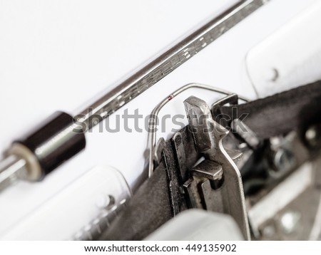 side view of typebar hits ink ribbon in old typewriter close up - stock photo