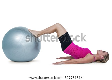 Side view of woman exercising with ball against white background
