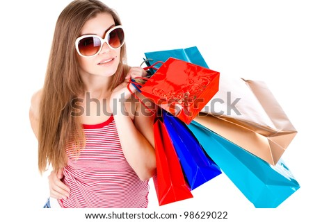 Side view of woman holding shopping bags against white background - stock photo