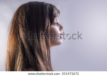 Side view of woman portrait over grey background with copy space