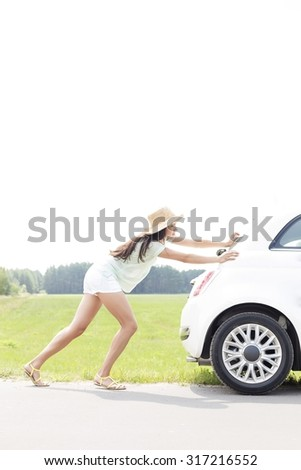 Side view of woman pushing broken down car on country road - stock photo
