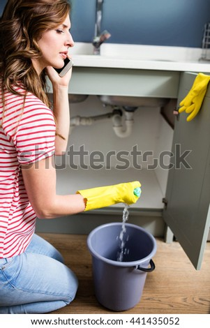 Side view of woman using cellphone while cleaning kitchen sink at home
