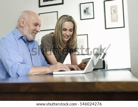 Side view of woman watching mature man use laptop at home office - stock photo