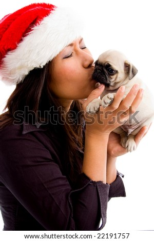 side view of woman with christmas hat and  kissing the puppy on an isolated background - stock photo