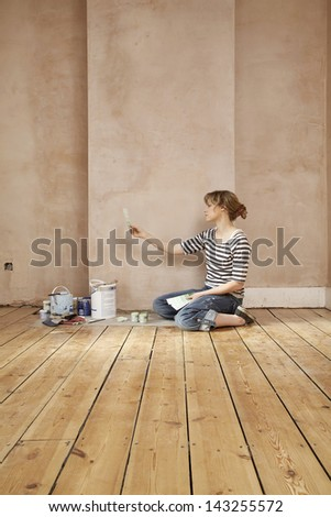 Side view of woman with painting tools choosing color from swatches in unrenovated room