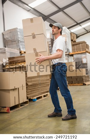Side view of worker carrying boxes in warehouse