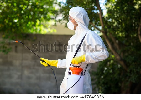 Side view of worker wearing protective suit using pesticide in back yard - stock photo