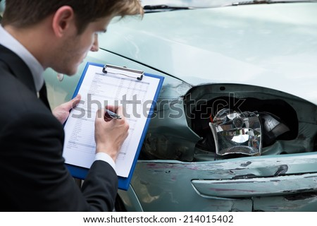 Side view of writing on clipboard while insurance agent examining car after accident - stock photo