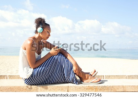 Side view of young african american black teenager girl sitting by sandy beach listening to music using headphones and smartphone against a blue sea and sky. Adolescent technology lifestyle outdoors. - stock photo
