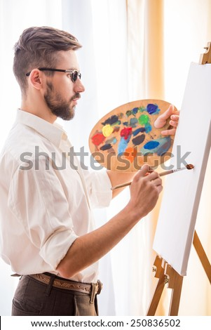 Side view of young artist  with brush and palette is going to painting a picture. - stock photo