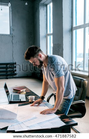 Side view of young bearded businessman looking down at projects