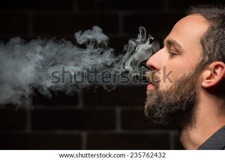 Side view of young bearded man is smoking against brick wall. - stock photo