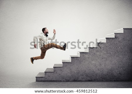 Side view of young bearded man running violently up the grey stairs isolated over white background with vignette