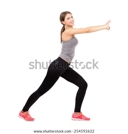 Side view of young beautiful slim sporty woman stretching and exercising. Full body length portrait isolated over white background. - stock photo