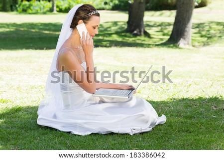 Side view of young bride using laptop and mobile phone while sitting on grass in park - stock photo