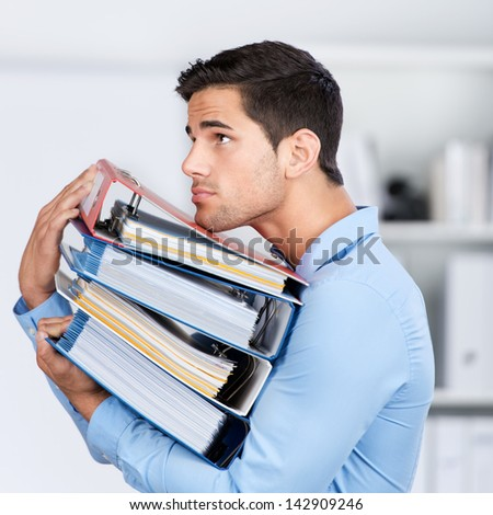 Side view of young businessman carrying stacked binders in office