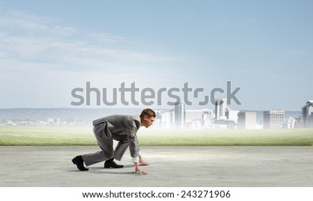 Side view of young businessman in start position ready to run