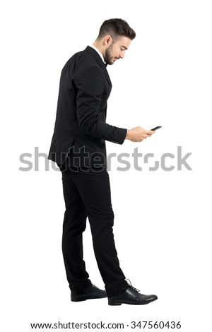 Side view of young businessman in suit typing message on smartphone touchscreen. Full body length portrait isolated over white studio background.  - stock photo