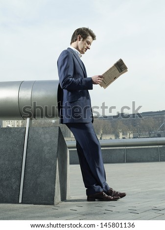 Side view of young businessman reading newspaper while leaning on pipe outdoors - stock photo