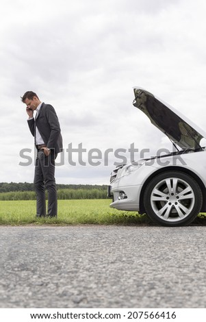 Side view of young businessman using cell phone by broken car at countryside - stock photo