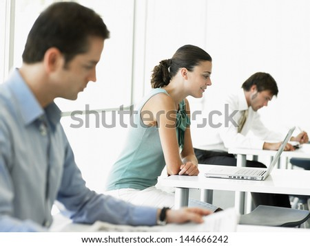 Side view of young businesswoman using laptop with male colleagues working in office - stock photo