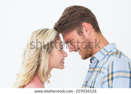 Side view of young couple looking at each other over white background - stock photo