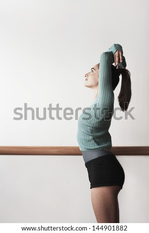 Side view of young female ballet dancer practicing at bar - stock photo