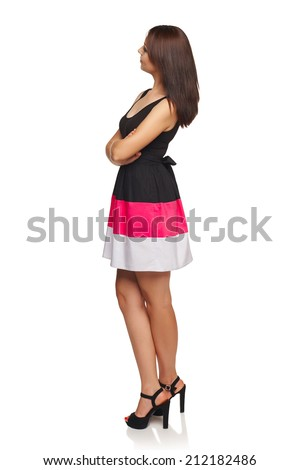 Side view of young female in dress standing full length looking away at blank copy space, looking away at blank space, isolated on white - stock photo