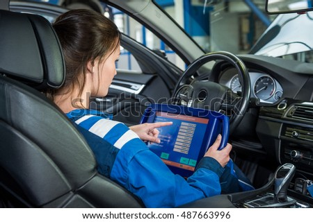 Side view young female mechanics using stock photo for Garage ad gap