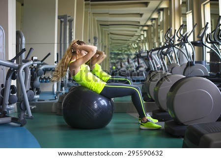 Side view of young fit woman doing sit-ups on exercise ball in gym - stock photo