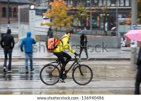 Side view of young man in protective gear with backpack riding bicycle on street - stock photo