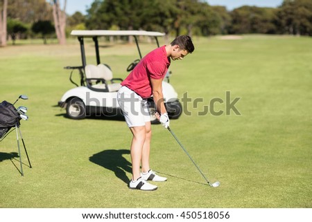 Side view of young man playing golf while standing on field - stock photo