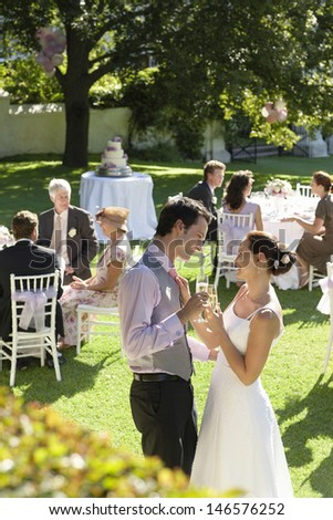 Side view of young newlywed couple toasting champagne while wedding guests sitting in garden - stock photo