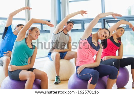 Side view of young people sitting on exercise balls and stretching out hands in the bright gym - stock photo