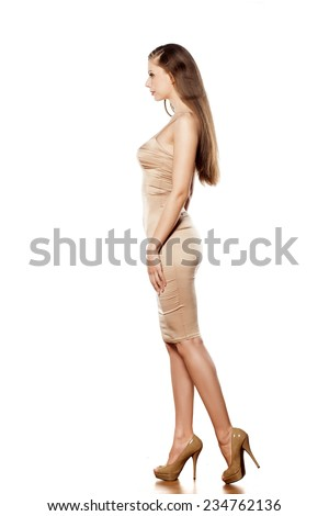 SIde view of young pretty woman in tight short dress posing on white background - stock photo