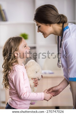 Side view  of young smiling female doctor and her little patient  with teddy bear. - stock photo